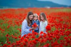 Härlig ung kvinna med barnflickan i vallmofält lycklig familj som har roligt i natur utomhus- stående i vallmo moder med fotografering för bildbyråer