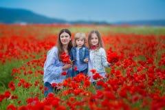Härlig ung kvinna med barnflickan i vallmofält lycklig familj som har roligt i natur utomhus- stående i vallmo moder med arkivfoton