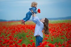 Härlig ung kvinna med barnflickan i vallmofält lycklig familj som har roligt i natur utomhus- stående i vallmo moder med royaltyfri bild