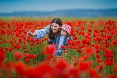 Härlig ung kvinna med barnflickan i vallmofält lycklig familj som har roligt i natur utomhus- stående i vallmo moder med arkivfoto