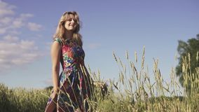 Härlig ung kvinna med blont hår som går på fält med högväxt gräs och ler på kameran långsam rörelse stock video