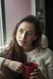 Härlig ung kvinna med brunt hår och ögon som dricker kaffe royaltyfri bild