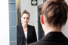 Härlig ung kvinna med bundet hår framme av spegeln arkivfoton