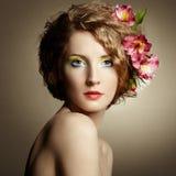 Härlig ung kvinna med delikata blommor i deras hår Arkivfoto