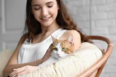 Härlig ung kvinna med den gulliga katten i fåtölj fotografering för bildbyråer