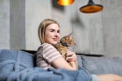 Härlig ung kvinna med den gulliga katten på soffan royaltyfri fotografi