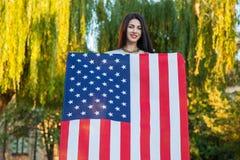 Härlig ung kvinna med den hållande amerikanska flaggan för klassisk klänning i parkera modemodell som rymmer oss som ler och ser  Royaltyfri Bild