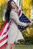 Härlig ung kvinna med den hållande amerikanska flaggan för klassisk klänning i parkera modemodell som rymmer oss som ler och ser  Arkivbild