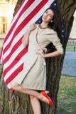 Härlig ung kvinna med den klassiska klänningen nära amerikanska flaggan i parkera modemodell som rymmer oss som ler och ser kamer Fotografering för Bildbyråer