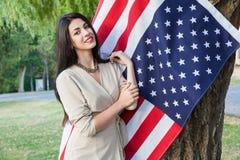 Härlig ung kvinna med den klassiska klänningen nära amerikanska flaggan i parkera modemodell som rymmer oss som ler och ser kamer Royaltyfria Bilder