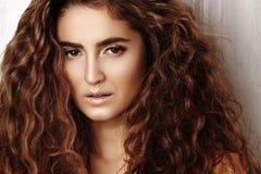 Härlig ung kvinna med den långa lockiga frisyren, modesmycken med brunetthår Indisk stilkläder, lång klänning royaltyfri fotografi