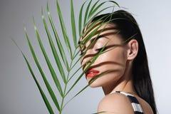 Härlig ung kvinna med den perfekta palmbladet för hudinnehavgräsplan Royaltyfria Foton