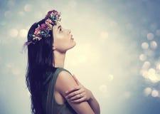 Härlig ung kvinna med en girland fotografering för bildbyråer