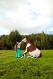 Härlig ung kvinna med en häst i fältet G Royaltyfri Foto