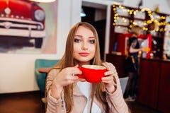 Härlig ung kvinna med en röd kopp kaffe på ett kafé Kvinna som dricker varmt lattekaffe på den hemtrevliga coffee shop Arkivbilder