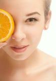 Härlig ung kvinna med en skiva av apelsinen Arkivbild
