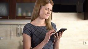Härlig ung kvinna med ett phabletanseende i kök Bläddra internet och le stock video