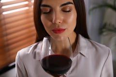 Härlig ung kvinna med exponeringsglas av lyxigt rött vin arkivbild