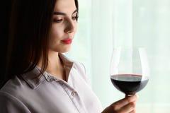 Härlig ung kvinna med exponeringsglas av lyxigt rött vin inomhus arkivbild