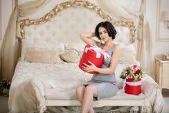 Härlig ung kvinna med gåvaasken hemma Royaltyfria Bilder