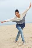 Härlig ung kvinna med gladlynt uttryck som går på stranden arkivbilder