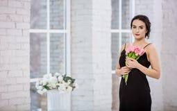 Härlig ung kvinna med gruppen av tulpan Arkivfoto
