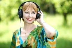Härlig ung kvinna med hörlurar royaltyfria bilder