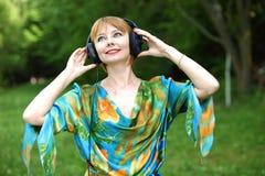 Härlig ung kvinna med hörlurar arkivbilder