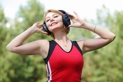 Härlig ung kvinna med hörlurar royaltyfri bild