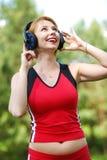 Härlig ung kvinna med hörlurar arkivfoto