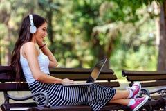 Härlig ung kvinna med hörlurar som sitter på bänk i parkera, genom att använda bärbar datordatoren Arkivfoto