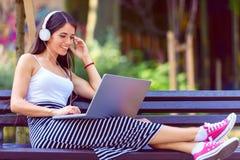 Härlig ung kvinna med hörlurar som sitter på bänk i parkera, genom att använda bärbar datordatoren Royaltyfri Fotografi