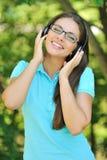 Härlig ung kvinna med hörlurar utomhus. Tycka om musik Arkivfoto