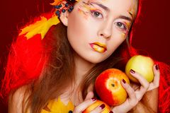 Härlig ung kvinna med höstsminket som över poserar i studio fotografering för bildbyråer