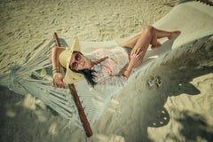 Härlig ung kvinna med hatten på den vita stranden, härligt landskap med kvinnan i Maldiverna, tropiskt paradis royaltyfri foto