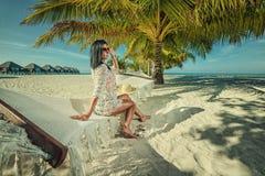 Härlig ung kvinna med hatten på den vita stranden, härligt landskap med kvinnan i Maldiverna, tropiskt paradis arkivfoto