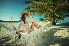 Härlig ung kvinna med hatten på den vita stranden, härligt landskap med kvinnan i Maldiverna, tropiskt paradis arkivbild