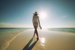 Härlig ung kvinna med hatten på den vita stranden, härligt landskap med kvinnan i Maldiverna, tropiskt paradis royaltyfria bilder
