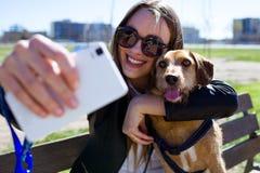 Härlig ung kvinna med hennes hund genom att använda mobiltelefonen arkivbild