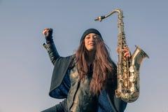 Härlig ung kvinna med hennes saxofon Arkivbilder