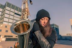 Härlig ung kvinna med hennes saxofon Royaltyfri Fotografi