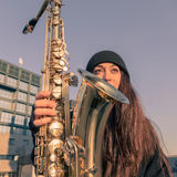 Härlig ung kvinna med hennes saxofon Arkivbild