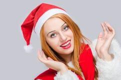 Härlig ung kvinna med jultomtenhatten som ler se lyckligt förvånat Arkivbild