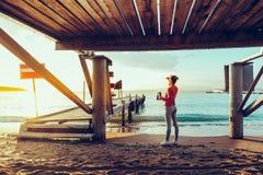 Härlig ung kvinna med kikare i handanseende vid havet nära den Pier And Enjoying View Of naturen royaltyfri bild