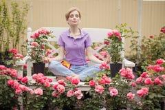Härlig ung kvinna med kort blont hår som mediterar rosor i trädgård arkivfoton