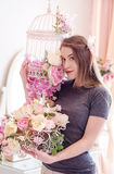 Härlig ung kvinna med långt blont hår, blåa ögon och att blomma buren, bärande t-skjorta Arkivbilder