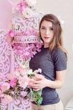 Härlig ung kvinna med långt blont hår, blåa ögon och att blomma buren, bärande t-skjorta Arkivfoto