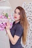 Härlig ung kvinna med långt blont hår, blåa ögon och att blomma buren, bärande t-skjorta Arkivbild