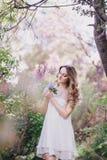 Härlig ung kvinna med långt lockigt hår i en trädgård med lilor Royaltyfri Fotografi
