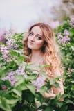 Härlig ung kvinna med långt lockigt hår i en trädgård med lilor Royaltyfri Foto
